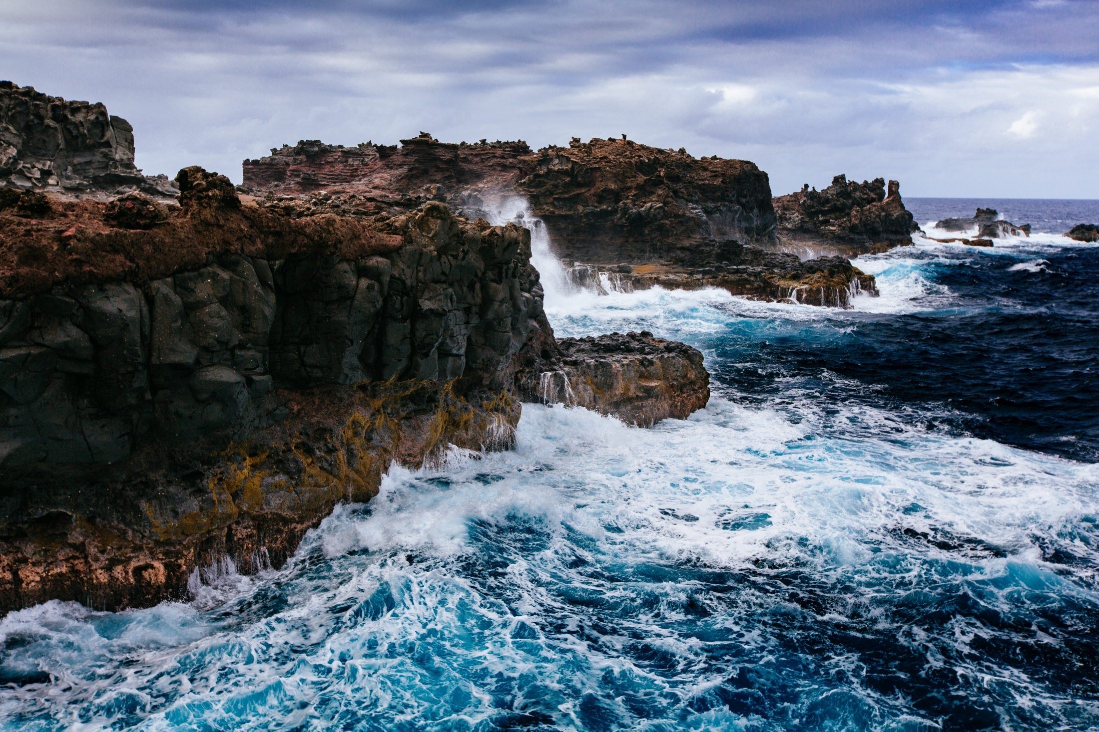 body of water crashing on brown rocks and cliff