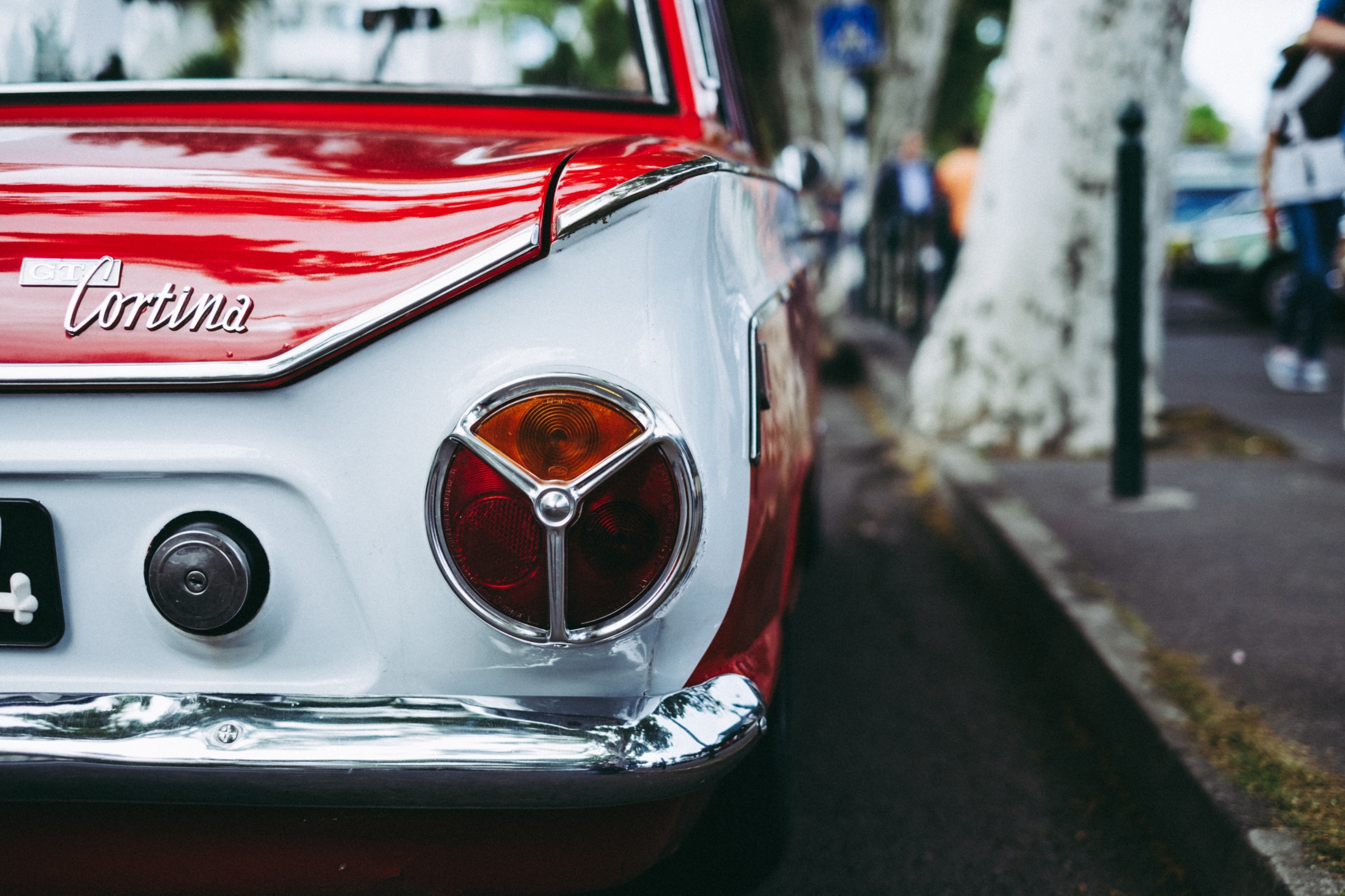 red and white Cortina car parked beside tree